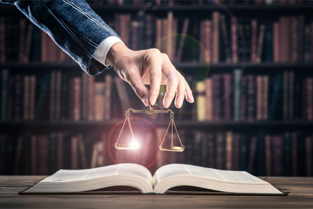 lawyer holding scales over open law book