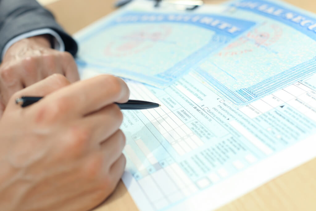 person filling out social security paperwork