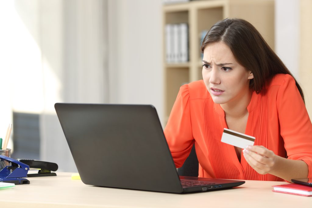 woman using a credit card on a laptop
